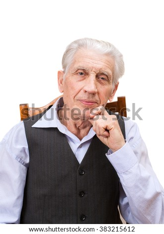 A senior man is sitting on armchair, isolated on white background