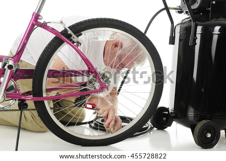 A senior man kneeling beside a girl's bike and an air compressor as he fill's his granddaughter's bike tire with air. On a white background. - stock photo