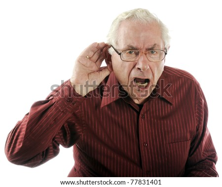 A senior man looking grumpy as he calls out and strains to here. - stock photo
