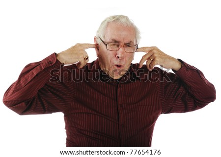 A senior man making a pained face while plugging his ears to block the noise.