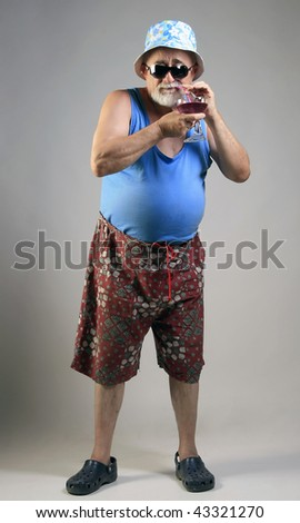 A senior man on a tropical vacation drinking cocktail - stock photo