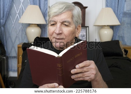 A senior man reads the King James Bible. - stock photo