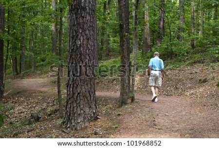 A senior man taking a walk in the forest.