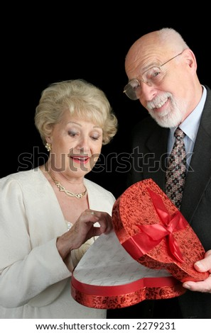 A senior man very proud of himself for surprising his wife with Valentine candy.  Black background. - stock photo