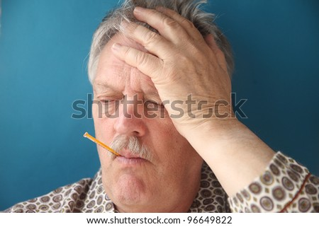 a senior man with a fever and aching head - stock photo