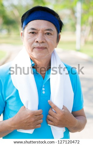 A senior man with a towel in the park - stock photo