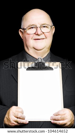 A senior pensioner with a grandfatherly kind-hearted face holds a clipboard with a blank white sheet of paper for your text or advertising in a marketing concept - stock photo
