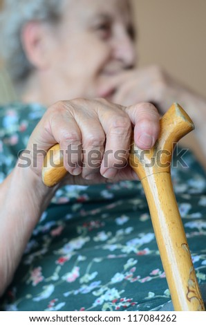 a senior person holding wooden cane in living room - stock photo