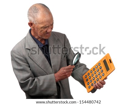A senior person uses a magnifying glass to assist him to view a calculator. - stock photo