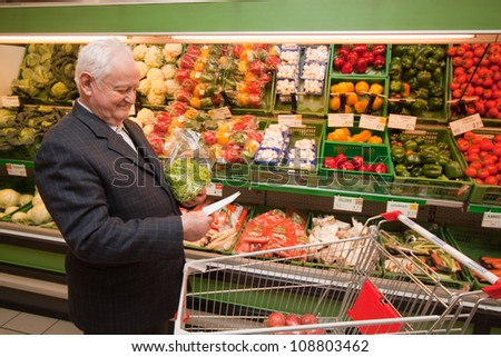 a senior shopping for food at the supermarket - stock photo