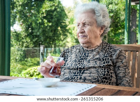 a senior woman holding a glass of tea at cafe - stock photo