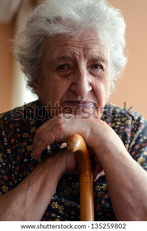 a senior woman leaning on wooden cane