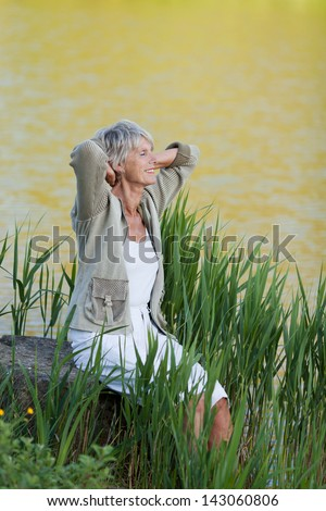 A senior woman sitting near a lake for fresh breathe and admiring the beauty of nature. - stock photo
