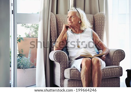 A senior woman sitting on her chair lost in thought - stock photo