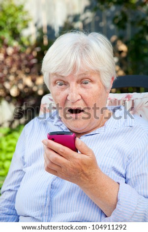 A senior woman stares stunned at something she sees on her smartphone.