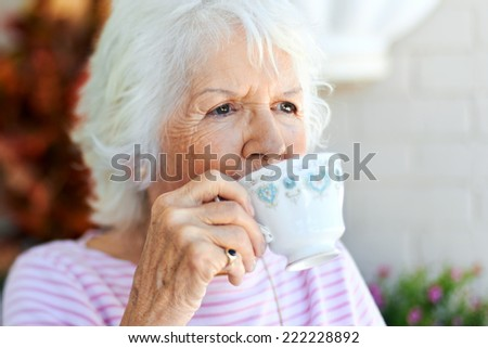 A senior woman taking a sip of her tea - stock photo