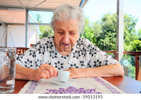 a senior woman tells fortune by inspecting the grounds remaining in her coffee cup - stock photo