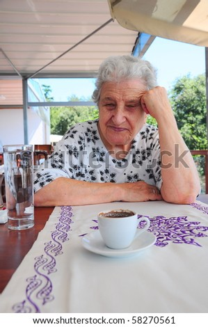 a senior woman thinking while drinking her coffee - stock photo