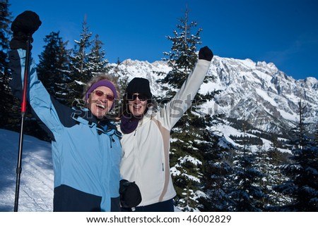 A senior woman with her daughter in a beautiful winter setting in the mountains. They are happily celebrating. - stock photo