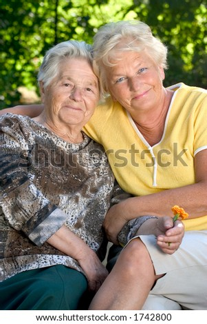 A senior woman with her 60 year old daughter hugging each other