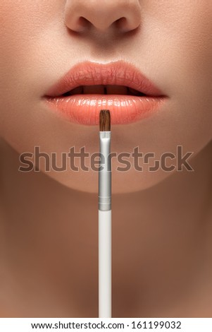 A sensual picture of woman lower face with makeup brush in front of lips. - stock photo