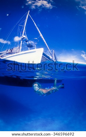A serene fitness model in a brightly colored bikini swimming under a bright white boat in bright blue water - stock photo