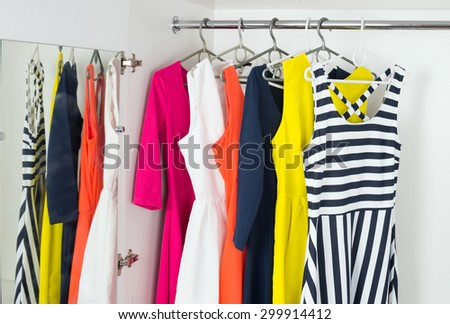 a series of bright modern fashion women's dresses on hangers in a white cupboard for summer and spring - stock photo