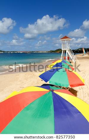 A series of colorful beach umbrellas on a Caribbean beach - stock photo