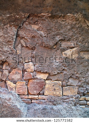 A series of irregularly shaped stones set into a wall - stock photo