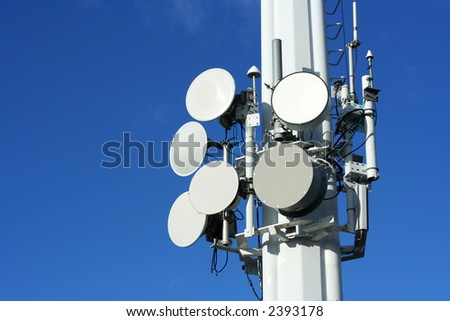A series of microwave, satellite, and cell phone dishes against a clear blue sky.