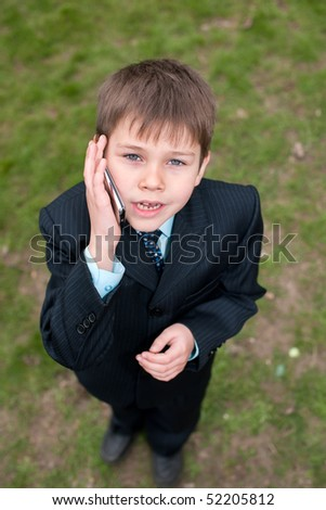 A serious boy in suit is speaking over the mobile while walking outside - stock photo