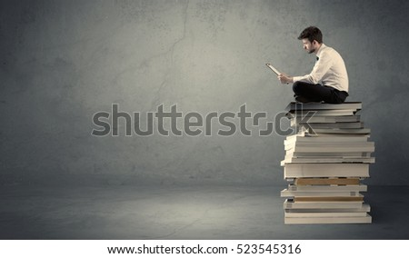 A serious businessman with laptop tablet in elegant suit sitting on a stack of books in front of dark grey background