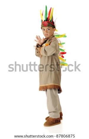 A serious elementary-aged boy beating his drum while wearing an American Indian warrior outfit.  One a white background. - stock photo