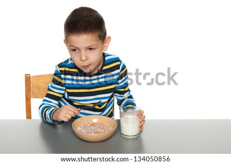 A serious little boy eats with a spoon his breakfast