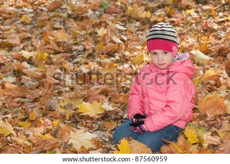 A serious little girl is sitting in the yellow leaves in autumn