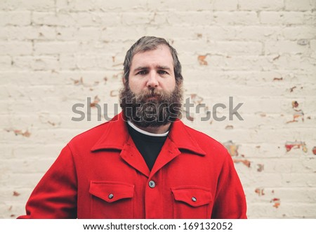 a serious looking man in front of a brick wall on a cold day vin - stock photo