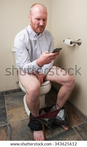 A serious man taking care of business on his phone in the bathroom - stock photo