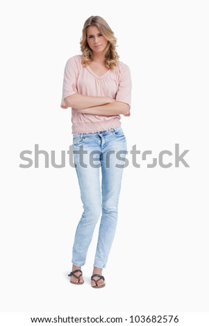 A serious woman is standing with her arms folded against a white background - stock photo