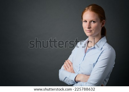 A serious young businesswoman poses for a portrait with folded arms. - stock photo