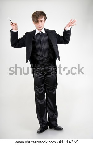 A serious young man in a black tailcoat with a stick is holding his hands up - stock photo