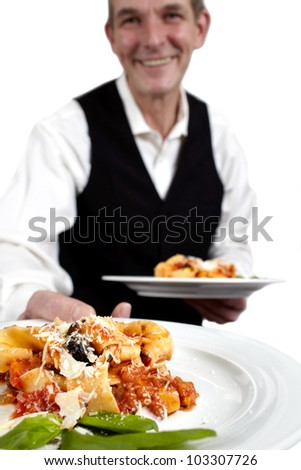 A servant is holding a plate with pasta, tomato sauce, parmesan and basil.? Focus on plate. Close-up.