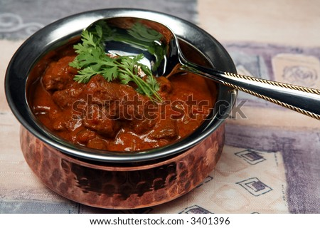 A serving bowl full of Madras butter beef curry. - stock photo