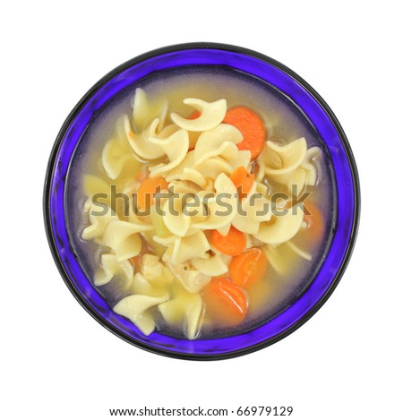 A serving of chicken soup with pasta and carrots in a colorful blue bowl on a white background. - stock photo