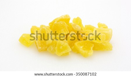 A serving of dried sugared pineapple chunks on a plastic cutting board. - stock photo