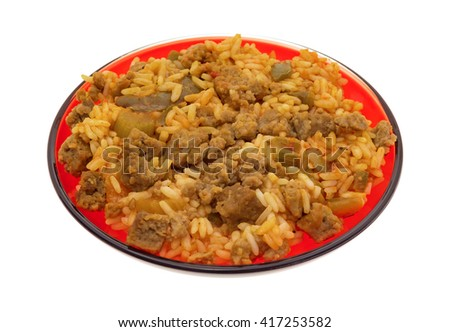 A serving of rice, green peppers and chunks of beef on a red plate isolated on a white background. - stock photo