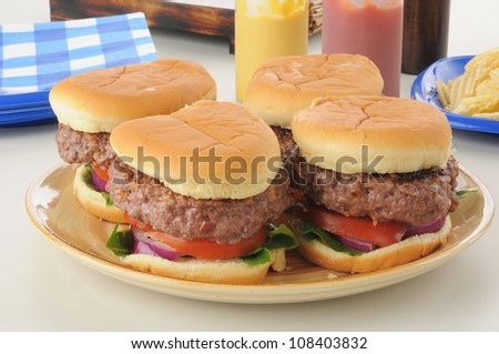 a serving platter of thick hamburgers with condiments - stock photo