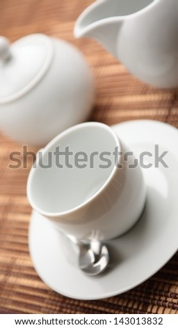 A set for serving coffee - a cup with a sugar holder and a small milk pitcher.