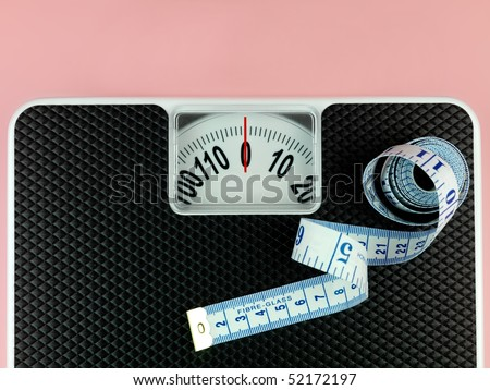 A set of bathroom scales isolated against a pink background - stock photo
