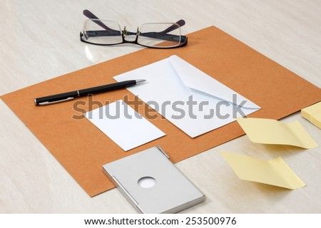 A set of blank envelopes with paper, pen, glasses, business card ans sticky notes side view - stock photo