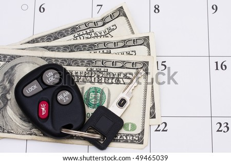 A set of car keys with cash on a calendar, Car Payment is due - stock photo